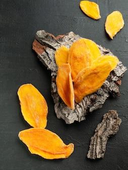 Сушеные ломтики манго. на коре дерева. вид сверху. темный фон.