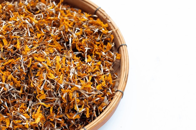 Dried marigold flower petals in bamboo basket on white background. flower herbal tea concept.