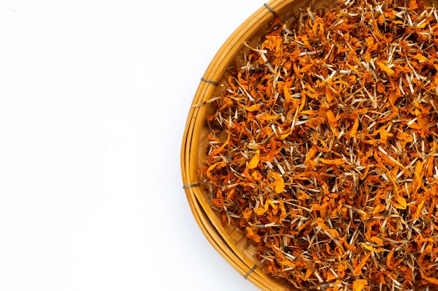Dried marigold flower petals in bamboo basket on white background.