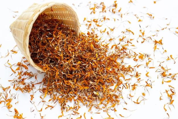 Dried marigold flower petals on white background. flower herbal tea concept.