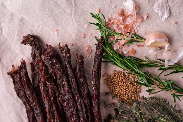 Вяленое мясо говядины вяленое мясо на скатерти и деревянной поверхности