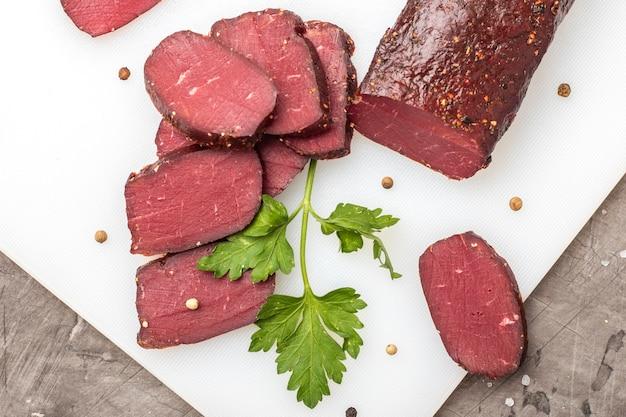 Сушеное мясо на разделочной доске с зеленью. вид сверху