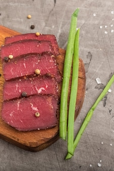 Сушеное мясо на деревянной разделочной доске и зеленом луке