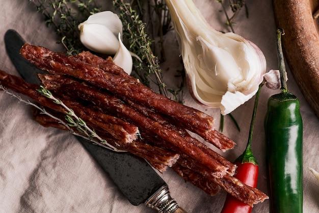 Вяленая свинина на скатерти и деревянной поверхности