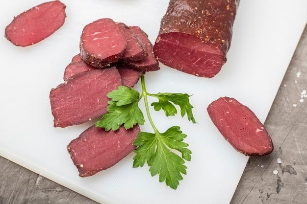 Сушеное мясо на разделочной доске с зеленью