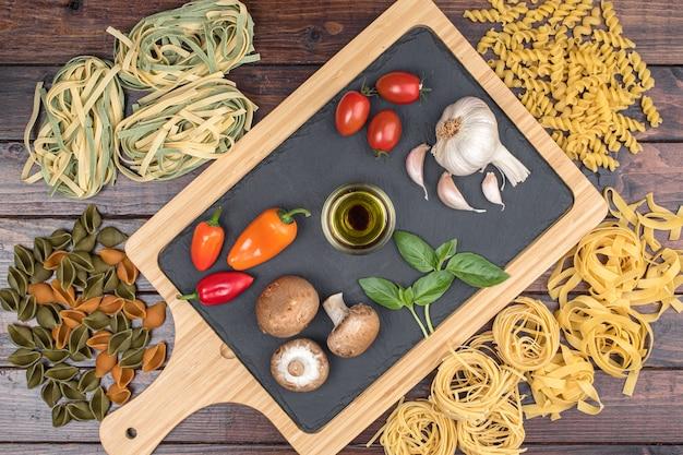 暗い木製のテーブルトップビューで乾燥した混合パスタと野菜。