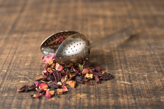 Dried mixture of herbal floral fruit tea with petals spilled from tea strainer on wooden plank