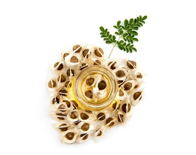 乾燥したモリンガの種子は、白い背景に分離されたハートの形と油を配置しました。