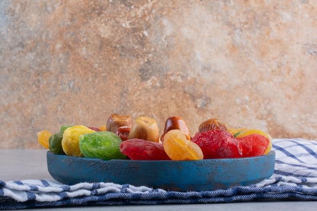 콘크리트 배경에 말린 여러 가지 빛깔의 체리와 열매.