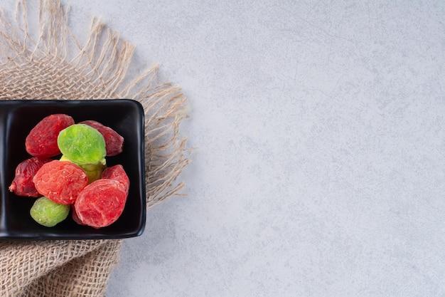 Gelatine di frutta essiccate multicolori isolate su priorità bassa concreta.