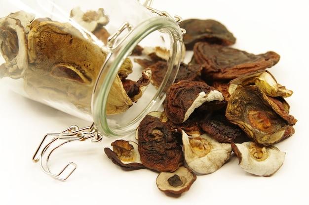 テーブルの上に散らばっているガラスの瓶の中の乾燥キノコ