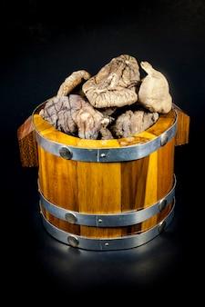 검은 배경에 나무 상자에 말린 버섯