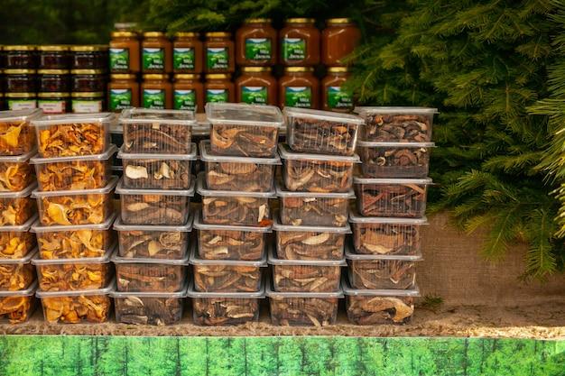 Сушеные грибы в пластиковых контейнерах на рождественской сельской ярмарке - лисички и белые грибы. лесное хозяйство.