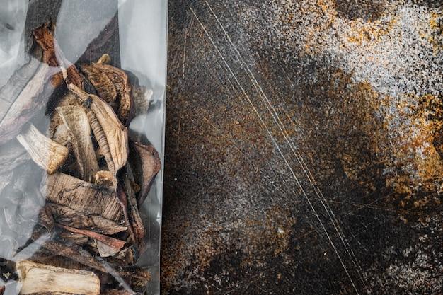 乾燥キノコセット、古い暗い素朴な背景、プラスチックパック、上面図フラットレイ、
