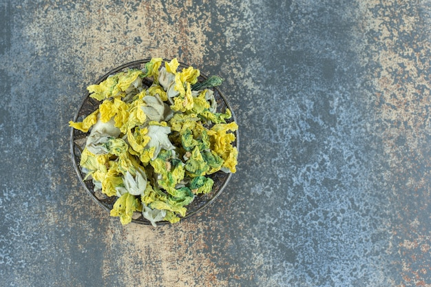 Fiori gialli naturali secchi in ciotola di metallo.