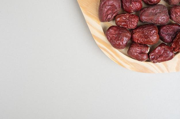 Frutta secca dell'olivastro sul piatto di legno