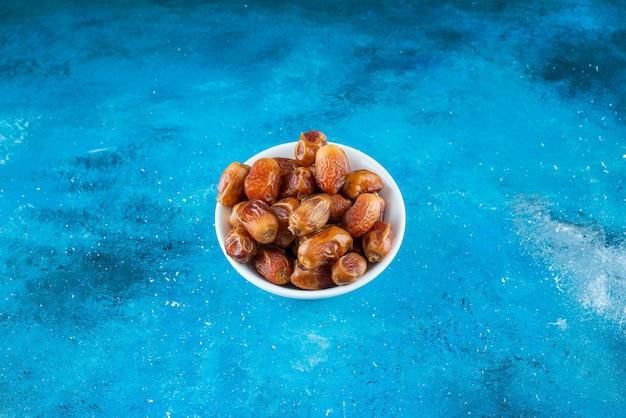 파란색 테이블에 그릇에 말린된 oleaster.