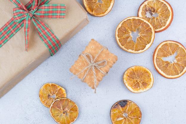 대리석 배경에 말린 오렌지, 비스킷 및 선물 상자.