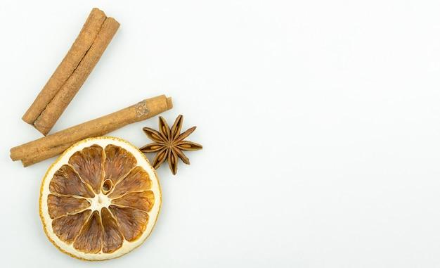 乾燥したオレンジ色のシナモンと白い背景の左側のアニス
