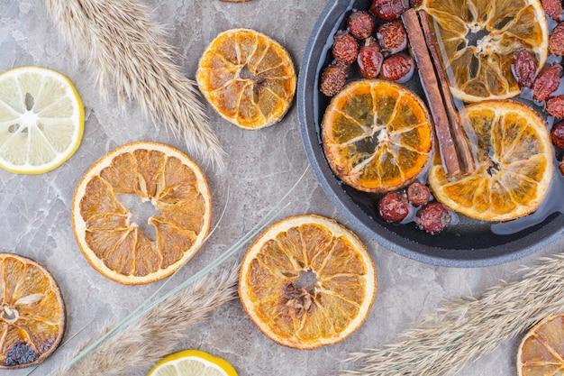 Fette di arancia e limone essiccate con cannella sulla superficie della pietra.