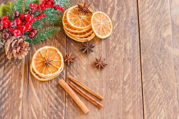 복사 공간이 있는 나무 테이블에 말린 오렌지 조각, 계피, 스타 아니스.