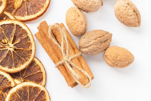 乾燥したオレンジスライス、シナモンスティック、クルミ。クリスマスのスパイス。新年のテーマ。セレクティブフォーカス。