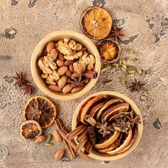 乾燥したオレンジスライス、シナモンスティック、アニススター、木製ボウルのカルダモンシード