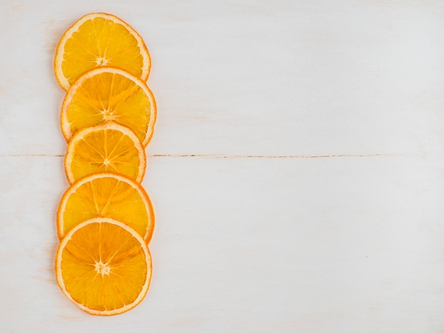 Dried orange slices or fruit chips close up on a white wooden background with copy space