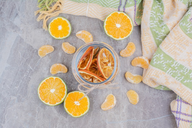 Dried orange slices in glass jar on stone surface.