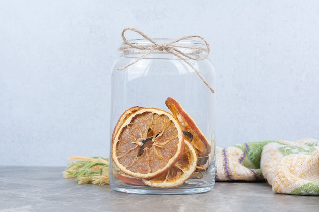 Dried orange slices in glass jar on stone table.