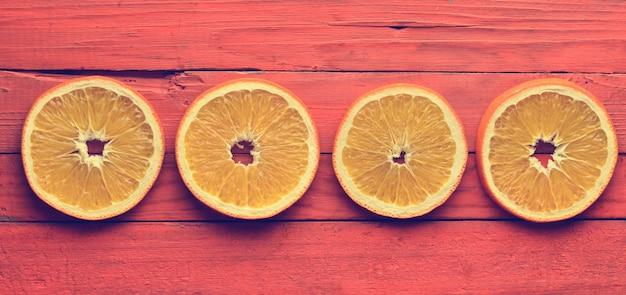 Dried orange slices on an orange wooden surface