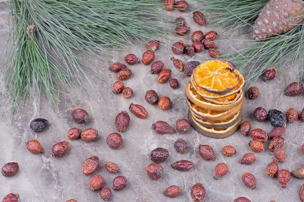 Fette d'arancia essiccate con fianchi su marmo.