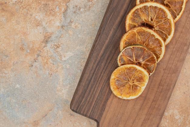 Dried orange slices on wooden board.