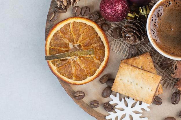 木の板にコーヒーの香りのカップと乾燥したオレンジ。高品質の写真