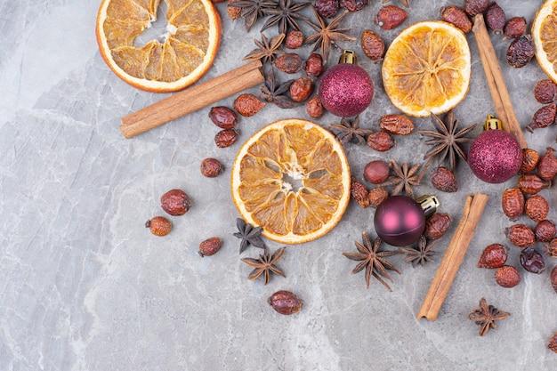 Сушеный апельсин с елочными шарами и шиповником на каменной поверхности.