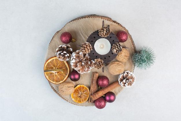 Сушеный апельсин с шишками и елочными шарами на деревянной тарелке. фото высокого качества