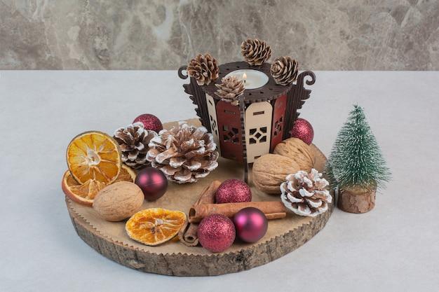 Arancia secca con pigne nelle quali e palle di natale sul piatto di legno. foto di alta qualità