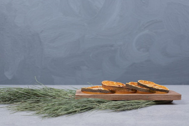 Dried orange on wooden board with branch of green tree.
