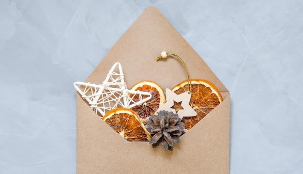 乾燥したオレンジ、クリスマスのおもちゃ、クラフト封筒のコーン