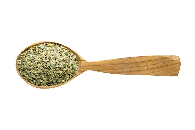 食品に加えるための乾燥オレガノ。白で隔離の木のスプーンのスパイス。美味しいお食事の調味料。