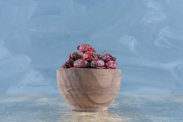 Dried organic rose hips in wooden bowl.