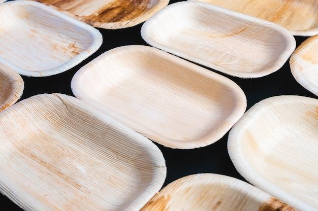 乾燥したヤシの葉またはビンロウの実と葉皿プレートの使い捨て食器製品、ゼロウェイスト環境コンセプト、黒の背景に自然環境に優しい有機食品包装。