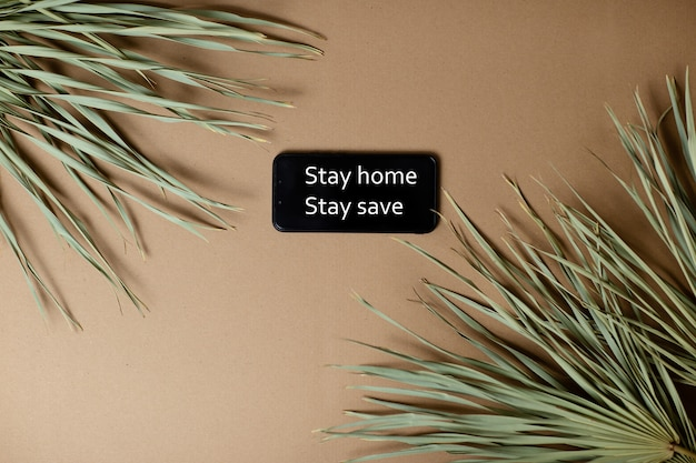 Dried palm leaves on craft paper background. smartphone with stay home stay safe text.