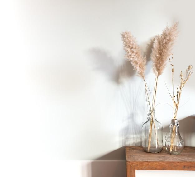흰 벽, 현대적인 밝은 장식 근처 나무 테이블에 유리 꽃병에 말린 팜파스 잔디