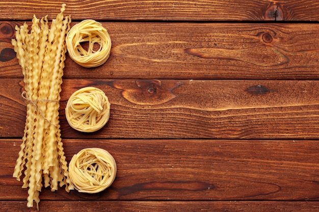 Dried pasta on wooden background