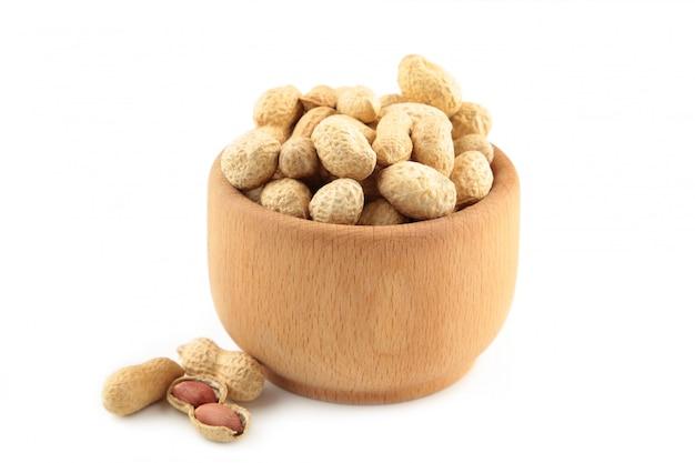 Сушеный арахис в деревянной миске, изолированные на белом фоне.