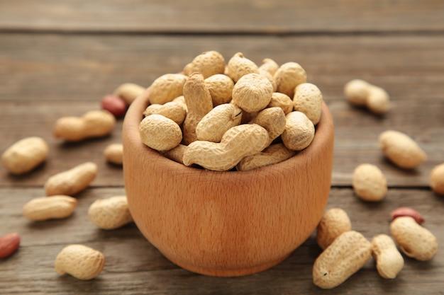 Сушеный арахис в деревянной миске на сером фоне.
