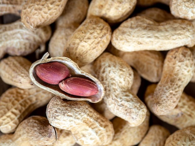 Dried peanuts in shells on peanuts background on wooden table. concept of snack