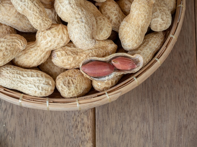 Dried peanuts in shells on peanuts background on wooden table
