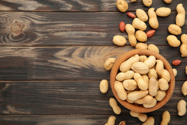 Dried peanuts in wooden bowl on brown background.